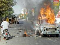 <p>An Indian man rides past a burning car during a riot in the city of Ahmedabad in the western state of Gujarat, May 5, 2002. REUTERS/Amit Dave</p>