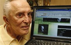 <p>L'attore Kirk Douglas posa davanti al pc con il suo sito su MySpace. REUTERS/Fred Prouser</p>