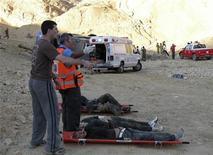 <p>Израильские спасатели кладут раненых туристов на носилки, Эйлат, 16 декабря 2008 года Автобус с российскими туристами упал в ущелье в Израиле во вторник, в результате чего по меньшей мере двадцать четыре человека погибли и десятки ранены, сообщает спасательная служба Израиля. REUTERS/Mori Chen (ISRAEL)</p>