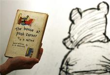 <p>An employee poses with the first American edition of A.A. Milne's Winnie-the-Pooh book 'The House at Pooh Corner' dated 1928 at Sotheby's in London December 15, 2008. REUTERS/Luke MacGregor</p>