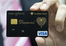 <p>Dmitry Nikolin, the Executive Director of Eurasian Bank, shows a new VISA card encrusted with a 0.02 carat diamond and laced with an elaborate gold pattern in Almaty, Kazakhstan, December 23, 2008. REUTERS/Shamil Zhumatov</p>