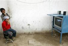 <p>Uighur children watch television in a Friday market in Yarkand, in the region of Xinjiang April 4, 2008. REUTERS/Nir Elias</p>