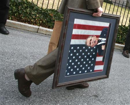 A member of the White House staff walks off with a portrait of outgoing U.S. President George W. Bush in Washington, January 13, 2009. REUTERS/Jason Reed