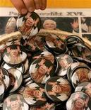 <p>Мужчина выбирает значок с изображением Папы Римского Бенедикта XVI в Марктле 22 апреля 2005 года. Папа Римский Бенедикт XVI стал одним из немногих людей преклонного возраста, кто открыл свой собственный канал на видео-хостинге YouTube. REUTERS/Alexandra Winkler</p>