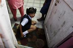 """<p>Rubina Ali, who acted in 'Slumdog Millionaire"""", removes her shoes after returning from school at her residence at a slum in the northern suburb of Bandra in Mumbai January 27, 2009. REUTERS/Arko Datta</p>"""
