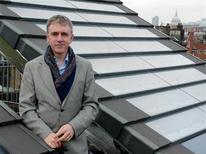 <p>Derry Newman, ad della britannica Solar Century, posa davanti a una batteria di pannelli solari progettati dalla sua società. REUTERS/Gerard Wynn</p>