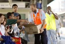 <p>Un dipendente delle ferrovie australiane distribuisce bottigliette di acqua gratis ai passeggeri in attesa alla stazione di Sydney per il grande acldo che sta colpendo il Paese in questi giorni. REUTERS/Tim Wimborne (AUSTRALIA)</p>