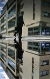 <p>A business man avoids puddles at the International Financial Services Centre - the business district of Dublin May 27, 2007. Picture was rotated 180 degrees. REUTERS/Luke MacGregor</p>