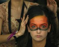 <p>A model has her hair adjusted backstage before the Shu Uemura show during the Singapore Fashion Festival March 26, 2007. REUTERS/Vivek Prakash</p>