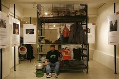 <p>Chau Kam-chuen, 55, a former caged home resident, poses with his former caged-bed inside a gallery as part of the Hong Kong Art Walk March 11, 2009. REUTERS/Bobby Yip</p>