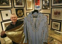 """<p>Anthony Sabestinas del sitio de internet gottahaveit.com muestra un overol y una capa de Elvis Presley que utilizó en el Madison Square Garden de Nueva York, 16 mar 2009. Algunos objetos de Elvis Presley entre los que se incluye un overol usado en sus presentaciones y un piano que tocó en su mansión, Graceland, salieron a remate el lunes en una muestra de su atractivo comercial a 31 años del fallecimiento del """"Rey"""". REUTERS/Brendan McDermid</p>"""