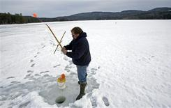 <p>Dan Seguin sets one of his lines while ice fishing on Pemigewasset Lake in New Hampton, New Hampshire March 7, 2009. REUTERS/Brian Snyder</p>