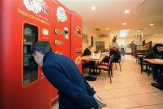 <p>An undated handout photo shows a boy watching a pizza being baked in a vending machine. REUTERS/Sitos/Handout</p>