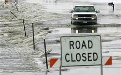 <p>A pickup truck travels a county road flooded by the Sheyenne River north of Fargo, North Dakota, March 29, 2009. REUTERS/Eric Miller</p>