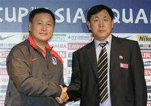 <p>South Korea's national soccer team head coach Huh Jung-moo (L) and North Korean national soccer team head coach Kim Jong-hun shake hands for the media during their joint news conference before their match at the Seoul World Cup Stadium March 31, 2009. REUTERS/Jo Yong-Hak</p>