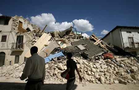 Residents walk past destroyed houses after an earthquake in the Italian village of Onna April 6, 2009. REUTERS/Alessia Pierdomenico
