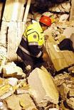 <p>Спасатель с собакой ищет людей под завалами разрушенного здания в Л'Аквиле 6 апреля 2009 года. Число жертв мощного землетрясения в центральной области Италии превысило 150 человек, более 1.500 ранены, до 50.000 остались без крова. REUTERS/Giampiero Sposito</p>