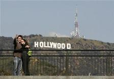 <p>Tourist Simon Boulet (L) takes a photo of himself and his girlfriend Estelle Lanoe in front of the Hollywood sign on Mount Lee while visiting Los Angeles from Paris, France as preparations continue for the 81st Academy Awards in Hollywood, California February 18, 2009. EUTERS/Danny Moloshok</p>