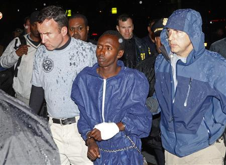 Abduhl Wali-i-Musi, accused of hijacking the Maersk Alabama and taking its captain Richard Philips hostage, is led into a federal building in New York April 20, 2009. REUTERS/Eric Thayer