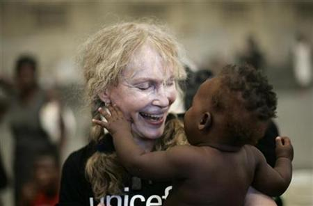 Actress Mia Farrow, a UNICEF goodwill ambassador, smiles as she holds a Haitian baby during her visit to a shelter in the town of Gonaives, September 20, 2008. REUTERS/ Eduardo Munoz