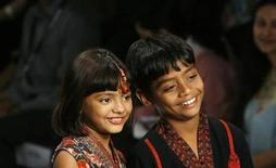 """<p>Azharuddin Ismail and Rubina Ali (L), actors in the film """"Slumdog Millionaire"""", display outfits designed by Ashima Leena during a fashion show on the second day of India Fashion Week in New Delhi March 19, 2009. REUTERS/Adnan Abidi</p>"""