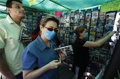 <p>Personas usan mascarillas mientras compran películas en Ciudad de México, 25 abr 2009. El brote de gripe porcina en México obligó a las principales cadenas de cine locales a cerrar las puertas de decenas de instalaciones en toda la capital del país. REUTERS/Eliana Aponte</p>