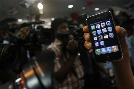 A customer shows the ''iPhone 3G'' after buying it at an outlet in New Delhi August 22, 2008. REUTERS/Adnan Abidi