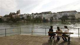 <p>Girls sit on a bench on the banks of the Rhine River, in front of the old town of the northern Swiss city of Basel, March 28, 2008. REUTERS/Arnd Wiegmann</p>