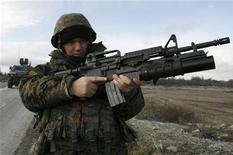 <p>Грузинский солдат патрулирует дорогу у границы с Южной Осетией 28 декабря 2008 года. Власти Грузии заявили во вторник о раскрытии заговора военных, обвинив Россию в попытке организации восстания на военной базе под Тбилиси. REUTERS/David Mdzinarishvili</p>