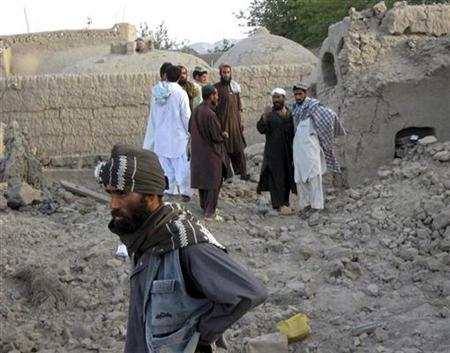 Villagers look at the destruction caused after air strikes in Ganj Abad of Bala Buluk district, in Farah province, May 5, 2009. REUTERS/Stringer