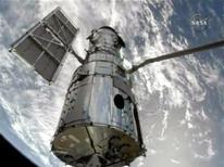 <p>Telescópio Hubble atracado ao braço mecânico do ônibus espacial Hubble visto do espaço em imagem da Nasa TV. Astronautas farão cinco caminhadas espaciais para reparar o telescópio. REUTERS/NASA TV</p>