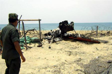 In this photograph released by the Sri Lankan military on May 17, 2009 shows what the army says is a government soldier looking at a destroyed Tamil Tiger boat on a beach inside the 'No Fire Zone' where they have surrounded the Tamil Tiger rebels for the final battle in a quarter-century conflict. REUTERS/Sri Lankan Government/Handout