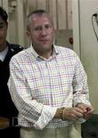 <p>Арестованный Майкл Брайан Смит входит в здание Уголовного суда в Бангкоке 21 мая 2009 года. Полиция Таиланда задержала в среду вечером британца, который подозревается в растрате порядка $150 миллионов своего работодателя в Дубай и был объявлен в розыск Интерполом. REUTERS/Sukree Sukplang</p>