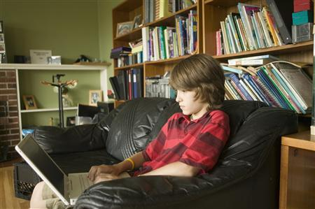 A 13-year-old uses a laptop in this undated handout photo. REUTERS/Newscom/Handout