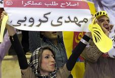 """<p>A supporter holds a placard that reads """"Practical Reformist, Mehdi Karroubi"""" during an election campaign at a stadium in Tehran, May 29, 2009. REUTERS/Raheb Homavandi</p>"""