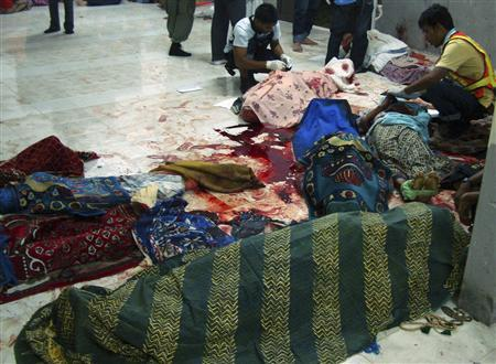 Officials inspect dead bodies of villagers after a shooting at a mosque in southern Thailand's Narathiwat province, June 8, 2009. REUTERS/Surapan Boonthanom