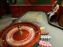 <p>Работник казино курит в пустом игровом зале в Киеве 18 мая 2009 года. Парламент Украины в четверг преодолел вето главы государства на закон о полном запрете игорного бизнеса в стране на период до принятия нового законодательства в этой сфере. REUTERS/Konstantin Chernichkin</p>