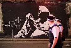 <p>Policiais olham grafite do artista Banksy em Londres. 23/06/2008. REUTERS/Finbarr O'Reilly</p>