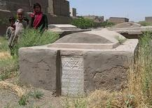 <p>Afghan children walk past a Jewish grave at a cemetry in Herat city June 8, 2009. REUTERS/ Mohammad Shoiab</p>