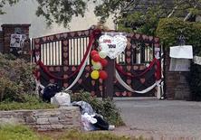 <p>Entrada do rancho de Michael Jackson recebe flores em homenagem ao cantor, cujo corpo será levado para Neverland. REUTERS/Phil Klein</p>