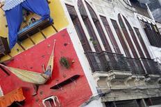 """<p>Los hermanos y artistas brasileños Tiago y Gabriel Primo """"colgados"""" en una pared en Río de Janeiro, 8 jul 2009. Dos hermanos brasileños le están dando un nuevo sentido artístico a la frase """"estar colgado"""", ya que comen, leen y duermen en la pared de un edificio en una ajetreada zona de Río de Janeiro para diversión de quienes los ven. Utilizando equipamiento de montañistas para maniobrar entre una cama, un escritorio, una hamaca y un antiguo gramófono, todo clavado a la pared, Tiago y Gabriel Primo llevan desde mayo pasando hasta 14 horas al día en su """"casa"""" en la pared de una galería de arte. REUTERS/Bruno Domingos</p>"""
