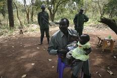 <p>Lord's Resistance Army (LRA) leader Joseph Kony holds his children during peace negotiations with Ugandan religious and cultural leaders in southern Sudan, November 30, 2008. REUTERS/Africa24 Media</p>