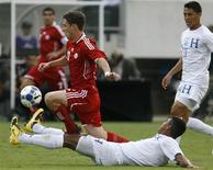 <p>Canada player William Johnson (L) is tackled by Honduras player Melvin Valladares (down) as teammate Roger Espinoza (R) looks on during their CONCACAF Gold Cup soccer quarterfinal match in Philadelphia, Pennsylvania, July 18, 2009. REUTERS/Tim Shaffer</p>