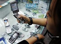 <p>Foto de archivo de una empleada de una tienda mostrando una serie de teléfonos móviles en Taipéi, 16 nov 2004. Un número cada vez mayor de adolescentes británicos está intercambiando imágenes de contenido sexual explícito de ellos mismos por teléfono móvil, lo que les expone al acoso de sus pares, dijeron el martes la policía y una organización de protección infantil. REUTERS/Richard Chung</p>