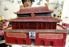 <p>Il parrucchiere cinese Huang Xin mostra la scultura della Porta della pace celeste, fatta interamente di capelli. REUTERS/David Gray (CHINA SOCIETY ODDLY IMAGES OF THE DAY)</p>