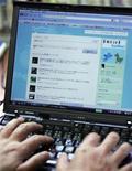 <p>Foto de archivo del legislador del partido Demócrata Seiji Ohsaka utilizando el servicio de internet Twitter en su oficina de Tokio, jun 29 2009. Twitter, la popular red social de Internet, quedó fuera de servicio el jueves tras un ataque de piratas informáticos, al tiempo que también se reportaron problemas en el sitio de su rival Facebook. REUTERS/Michael Caronna</p>