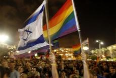 <p>Israelis wave rainbow flags as they attend a rally against the recent shooting attack in Tel Aviv August 8, 2009. REUTERS/Ronen Zvulun</p>