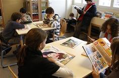 <p>Dei bambini impegnati a leggere nella biblioteca di una scuola. REUTERS/Charles Platiau</p>