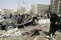 <p>Женщина проходит мимо взорванного автомобиля у здания министерства иностранных дел Ирака в Багдаде 19 августа 2009 года. Как минимум 75 человек погибли и 310 получили ранения в результате взрывов и минометных обстрелов в центре Багдада в среду, сообщила иракская полиция. REUTERS/Bassim Shati</p>