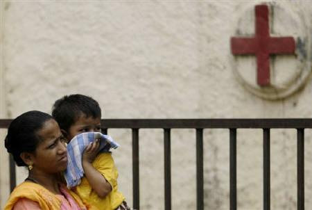 A woman carries a child outside a hospital in Mumbai August 9, 2009.  REUTERS/Punit Paranjpe